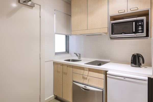 kitchen with modern appliances including kettle, microwave, bar fridge and dishwasher in Studio Apartment at Oaks Broome hotel in Western Australia