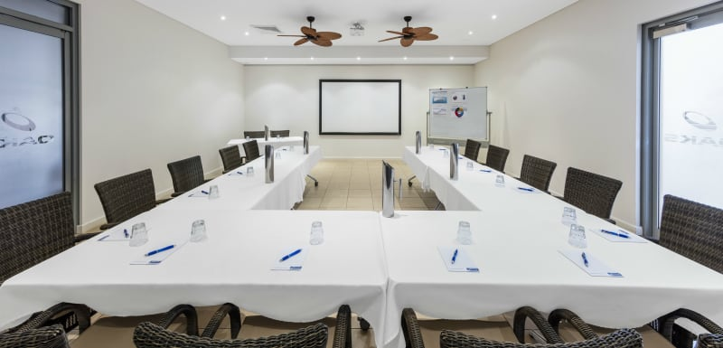 tables and chairs arranged in air conditioned conference room for hire with projector in Broome, WA