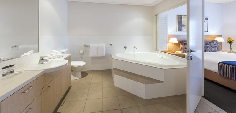 large en suite bathroom with clean towels, spa bath, toilet and large mirror in 1 Bedroom Apartment at Oaks Broome hotel in Western Australia