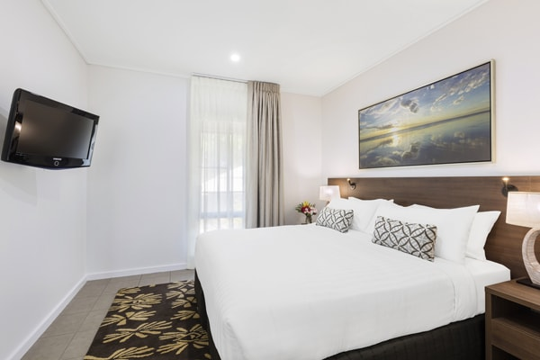 TV with Foxtel on wall of air conditioned 2 Bedroom Apartment with comfortable double bed at Oaks Cable Beach Sanctuary hotel in Broome, Western Australia