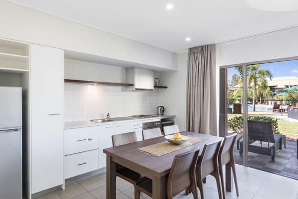 open plan kitchen with dining table, microwave, big fridge, large freezer and stove top cooker plates in 2 Bedroom Apartment at Broome hotel in Western Australia