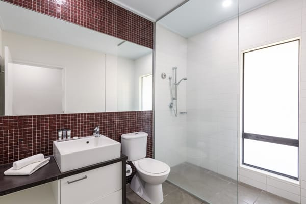 clean en suite bathroom with toilet, big shower, large mirror and fresh towels in 3 Bedroom Villa at Oaks Cable Beach Sanctuary hotel in Broome, Western Australia