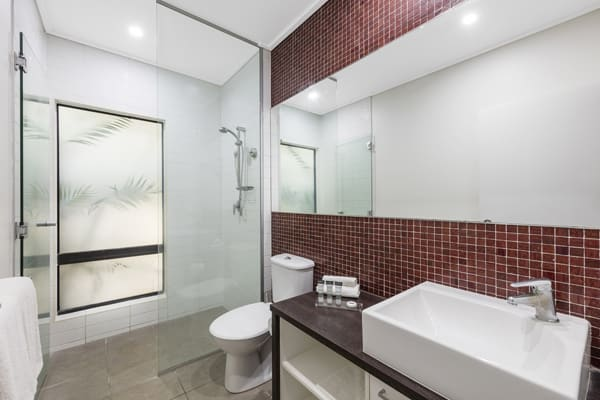 large en suite bathroom with toilet, clean towels and disabled access shower in hotel Studio accommodation in Broome, Western Australia