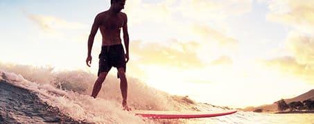 man surfing on wave on Gold Coast, Australia at sunset