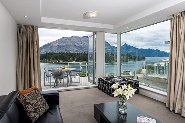 hotel accommodation living room with modern, comfortable couches and large glass sliding doors leading to big private balcony with views of Queenstown mountains in New Zealand