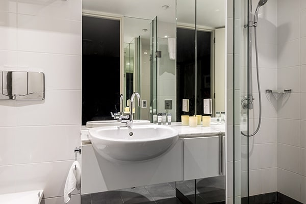 clean en suite bathroom with disabled access shower, toilet and fresh white towels for guests staying in a 2 Bedroom Apartment at Oaks Club Resort hotel in Queenstown, New Zealand