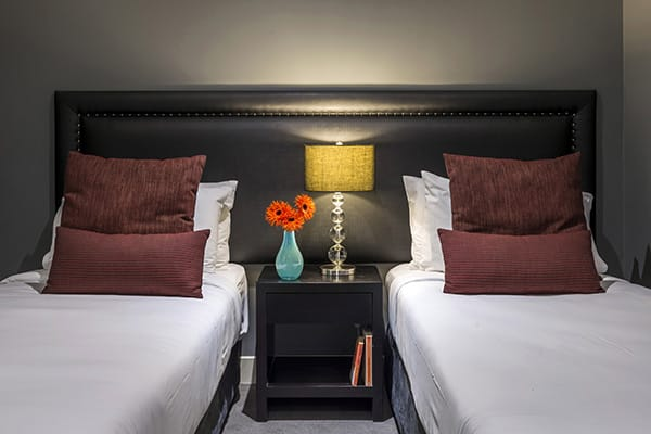 second room of 2 Bedroom hotel apartment accommodation with two comfortable single beds and Wi-Fi access in Queenstown, New Zealand