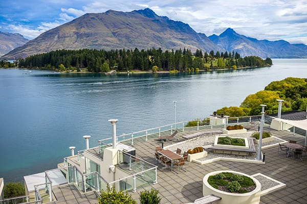 panoramic aerial view jet boats on Lake Wakatipu in Queenstown, New Zealand from private balcony of 2 Bedroom Apartment at Oaks Club Resort hotel
