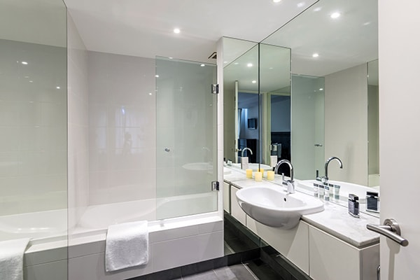 large en suite bathroom with toilet, adjustable shower and bath tub in 2 Bedroom Apartment with heating and air conditioning in Queenstown, New Zealand