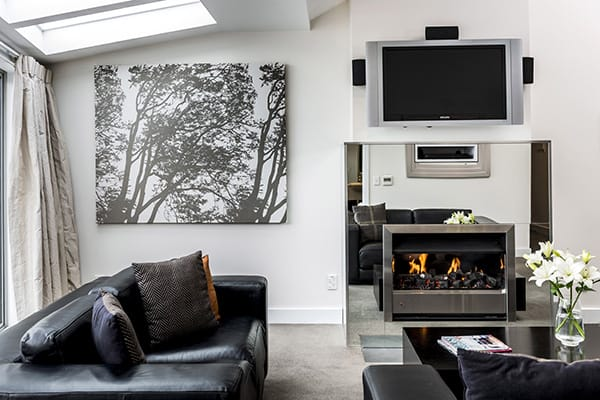 large, well lit living room with Sky TV, fireplace, comfortable leather couches and internal heating in 2 Bedroom Lake View Apartment at Oaks Club Resort hotel in Queenstown, New Zealand