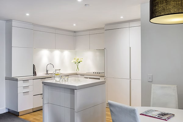 open plan dining room and kitchen with microwave, dishwasher, large refrigerator, freezer, toaster and kettle in 2 Bedroom Apartment in Queenstown hotel, New Zealand