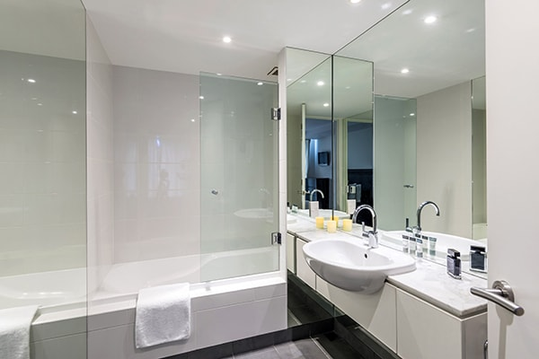 en suite bathroom of 3 Bedroom Lake View Apartment with shower, bathtub, toilet and clean towels at Oaks Club Resort hotel in Queenstown, New Zealand