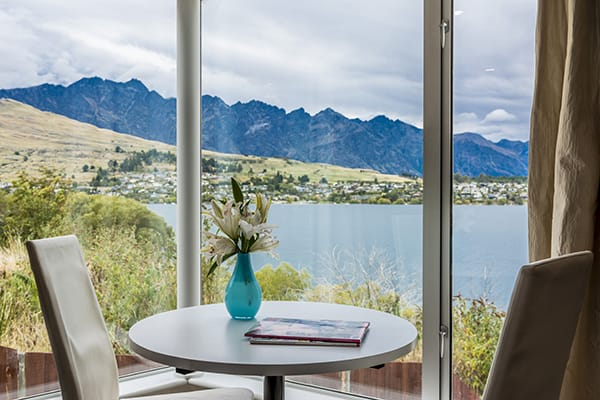 vase with flowers on table next to big window with views of snow capped mountains of Queenstown in 3 Bedroom Apartment at Oaks Club Resort hotel