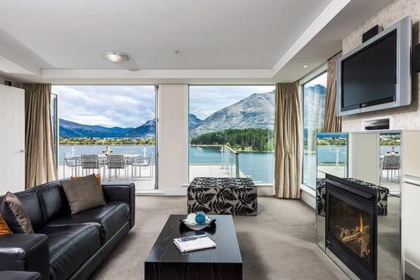 3 bedroom hotel apartments big living room with Sky TV, leather couches, fireplace and big balcony outside overlooking Lake Wakatipu in Queenstown, NZ