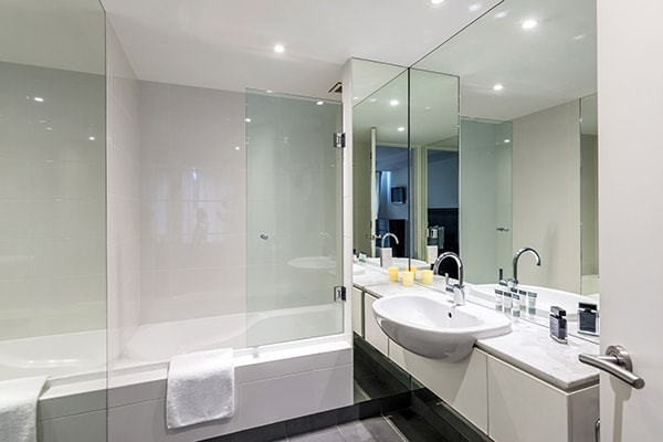 large en suite tiled bathroom with clean towels, big mirror, toilet and shower in family friendly 4 Bedroom Apartment at Oaks Club Resort hotel, Queenstown, New Zealand