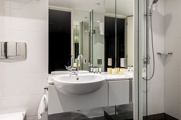 clean en suite bathroom with disabled access shower, toilet, bath and large mirrors in Hotel room holiday apartment at Oaks Club Resort, Queenstown, New Zealand