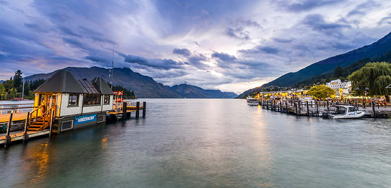 speed boats and yachts on Lake Wakatipu at sunset in Queenstown, New Zealand during winter