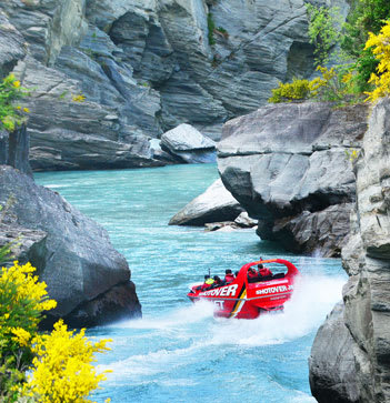 high speed jetboat with tourist passengers going down Queenstown river with cliffs either side in New Zealand