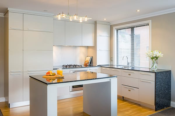 large open plan kitchen with refrigerator, freezer, oven, microwave, kettle and toaster for guests staying in a 1 bedroom hotel apartment at Oaks Shores resort in Queenstown, New Zealand