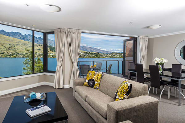 Living room with large windows and views of Lake Wakatipu in 1 bedroom holiday apartment with Wi-Fi at Oaks Shores hotel in Queenstown, New Zealand