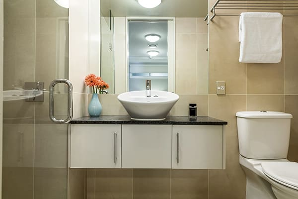 clean en suite bathroom in 2 bedroom holiday apartment with big mirror, fresh towels, toilet and disabled access shower at Oaks Shores hotel in Queenstown, New Zealand