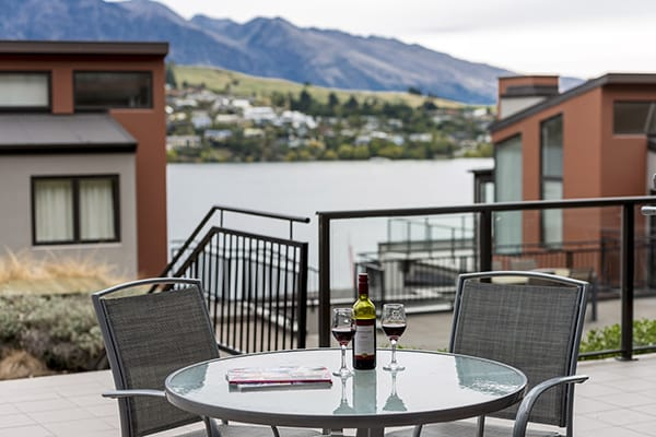 bottle of wine and two glasses with vegan menu option on table in courtyard outside 2 bedroom holiday apartment at Oaks Shores hotel in Queenstown, New Zealand