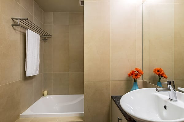 large en suite bathroom with clean towels, bath tub, shower and toilet in 2 bedroom, child friendly holiday apartment in Queenstown, New Zealand
