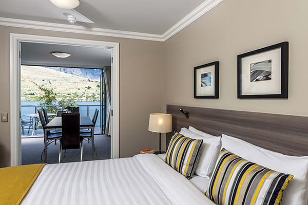 comfortable double bed with big pillows and clean sheets in master room with Wi-Fi in 2 bedroom holiday apartment at Oaks Shores hotel in Queenstown, New Zealand