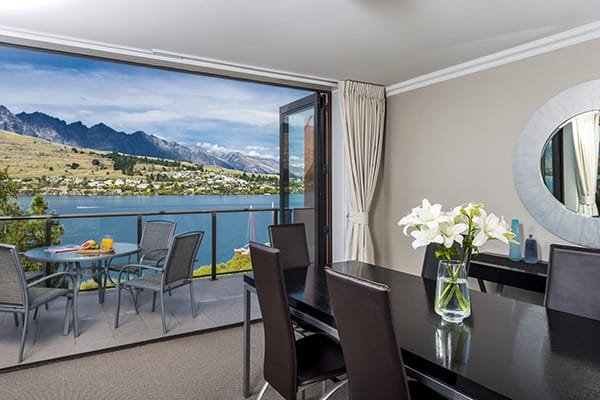 large dining room table with chairs and glass doors opening to big private balcony with beautiful views of speed boats on Lake Wakatipu and The Remarkables mountain range in Queenstown