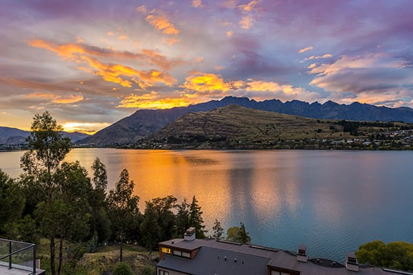 beautiful sunset over The Remarkables mountain range and Lake Wakatipu during summertime in Queenstown, New Zealand