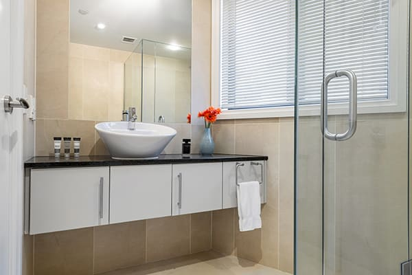 clean en suite bathroom with shower, toilet, large mirror, heating and fresh towels in 4 Bedroom Penthouse holiday accommodation at Oaks Shores hotel in Queenstown, New Zealand