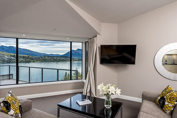 large flat screen television with Sky TV in spacious living room with comfortable couches and big windows with views of The Remarkables mountains and Lake Wakatipu