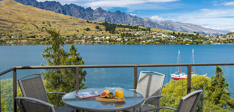 healthy fruit breakfast on table at hotels Queenstown on private balcony of hotel apartment overlooking boats on Lake Wakatipu at Oaks Shores resort in Queenstown, New Zealand