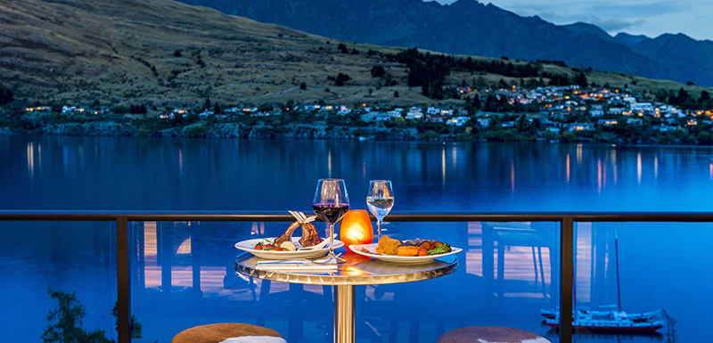 steak, salad and wine glasses on table in romantic setting with candles and moonlight shining onto Lake Wakatipu in Queenstown, New Zealand