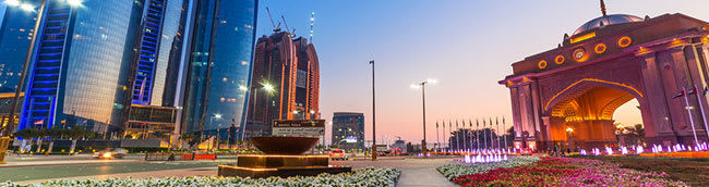 Abu Dhabi city at sunset with flower gardens and temples along busy streets filled with overseas tourists