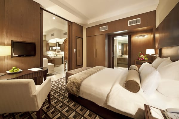 big bedroom with comfortable bed, clean sheets and en suite bathroom in Deluxe Suite at Oaks Liwa Executive Suites hotel in Abu Dhabi, United Arab Emirates