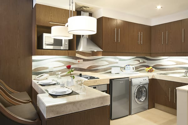 kitchen with microwave, dishwasher, fridge, kettle and toaster in Deluxe Suite of Oaks Liwa Executive Suites holiday apartments hotel in Abu Dhabi, United Arab Emirates