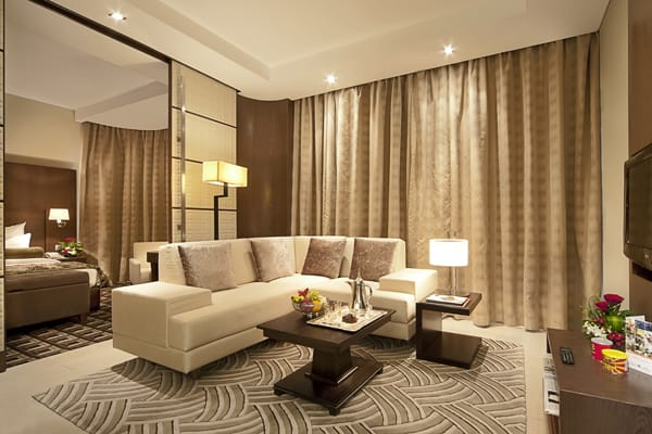 big living room of Deluxe Superior Suite hotel apartment with TV, Wi-Fi and air conditioning at Oaks Liwa Executive Suites in Abu Dhabi city centre in United Arab Emirates