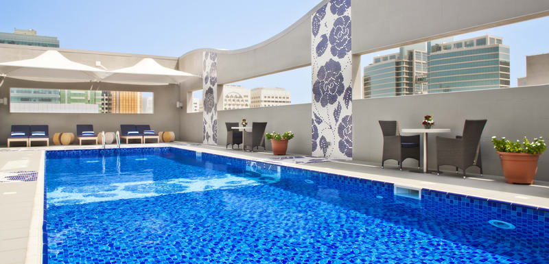 large swimming pool for guests staying at Oaks Liwa Executive Suites hotel to swim in while visiting Abu Dhabi on holiday in the United Arab Emirates