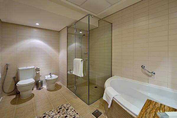 en suite bathroom with toilet, bidet, big shower, bath tub and clean towels in 2 Bedroom holiday apartment at Oaks Liwa Heights hotel in Dubai, United Arab Emirates