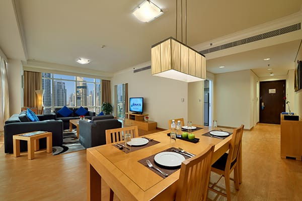 dining table with plates and cutlery in large living room in 2 Bedroom holiday apartment with air con and Wi-Fi at Oaks Liwa Heights hotel in Dubai, United Arab Emirates
