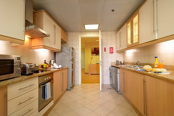 kitchen with microwave, oven, kettle, fridge, freezer and toaster in 2 Bedroom holiday apartment with air con at Oaks Liwa Heights hotel in Dubai, United Arab Emirates