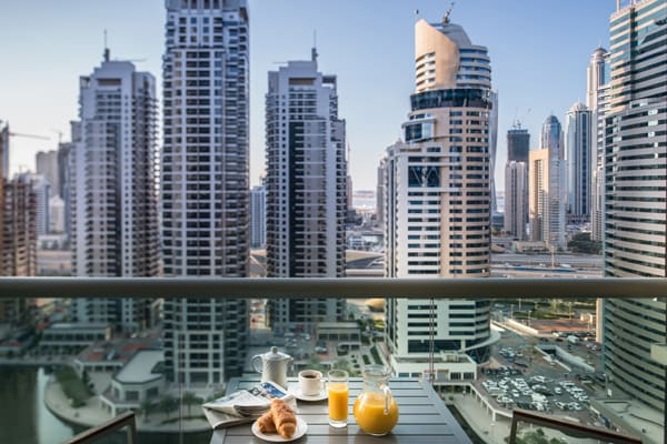 private balcony with beautiful views of Dubai and vegetarian breakfast menu option on table at Oaks Liwa Heights hotel in Dubai, United Arab Emirates